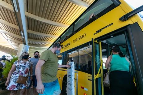 Turistas embarcam no ônibus de turismo fazendo uso de álcool em gel, no Centro de Recepção de Visitantes da Margem Esquerda da Itaipu Binacional.